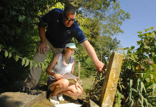 In this Sept. 18, 2018 photo, Prairie Central High School sophomore Abby Bergstralh along with  teacher Andrew Quain, work as she attempts to read the name on an Avoca Cemetery headstone north of Fairbury, Ill. Quain's students were making a map of graves in the historic cemetery. (David Proeber/The Pantagraph via AP)