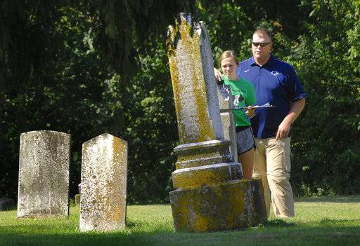 In this Sept. 18, 2018 photo, Prairie Central High School teacher Andrew Quain works with  sophomore Ashlyn Kratochvil, as she mapped a headstone with a GPS device in the Avoca Cemetery north of Fairbury, Ill. Quain's students are hoping to create a map that will enable cemetery visitors to find those buried there. (David Proeber/The Pantagraph via AP)