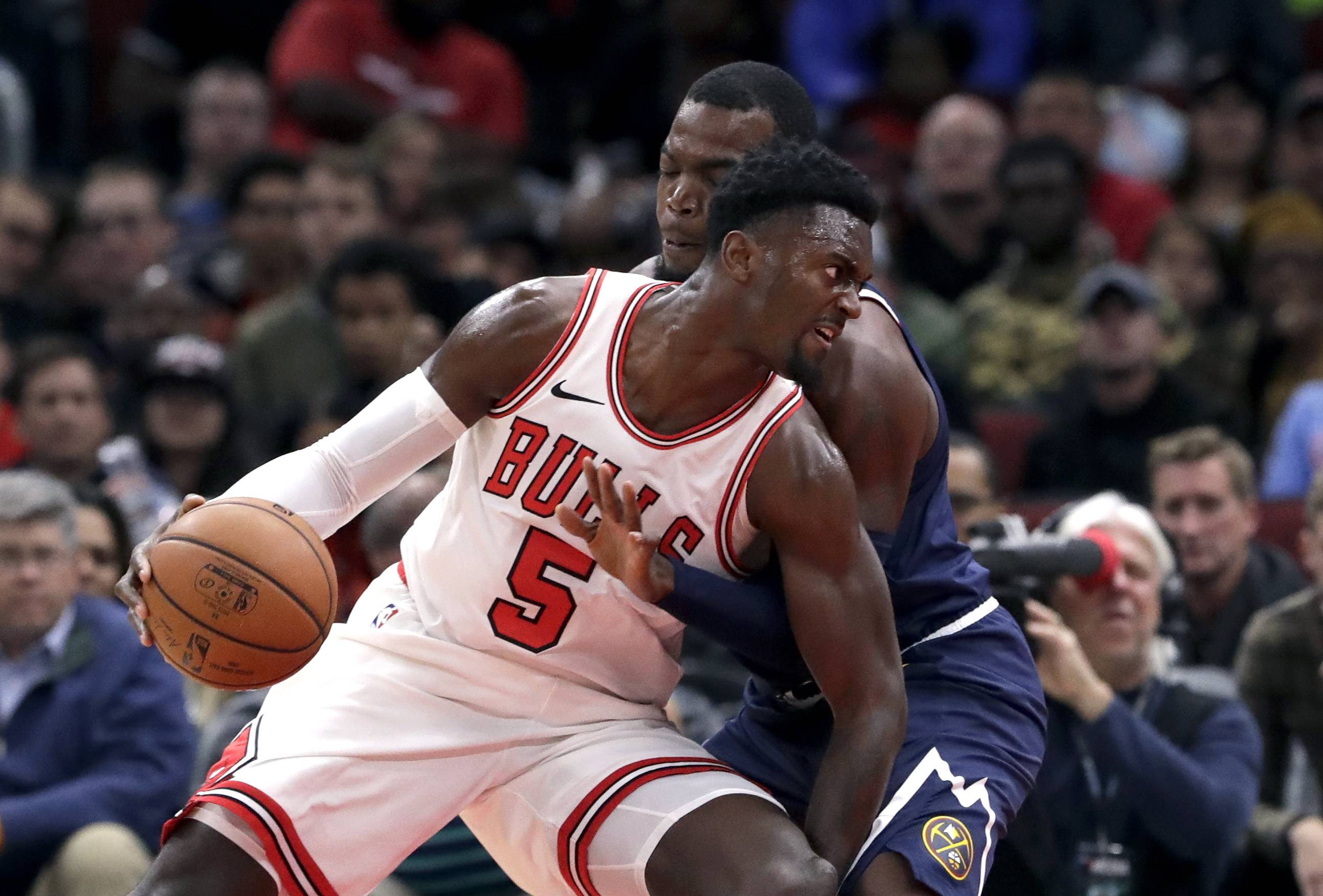 Chicago Bulls forward Bobby Portis (5) drives against Denver Nuggets forward Paul Millsap during the first half of an NBA preseason basketball game Friday, Oct. 12, 2018, in Chicago. (AP Photo/Nam Y. Huh)