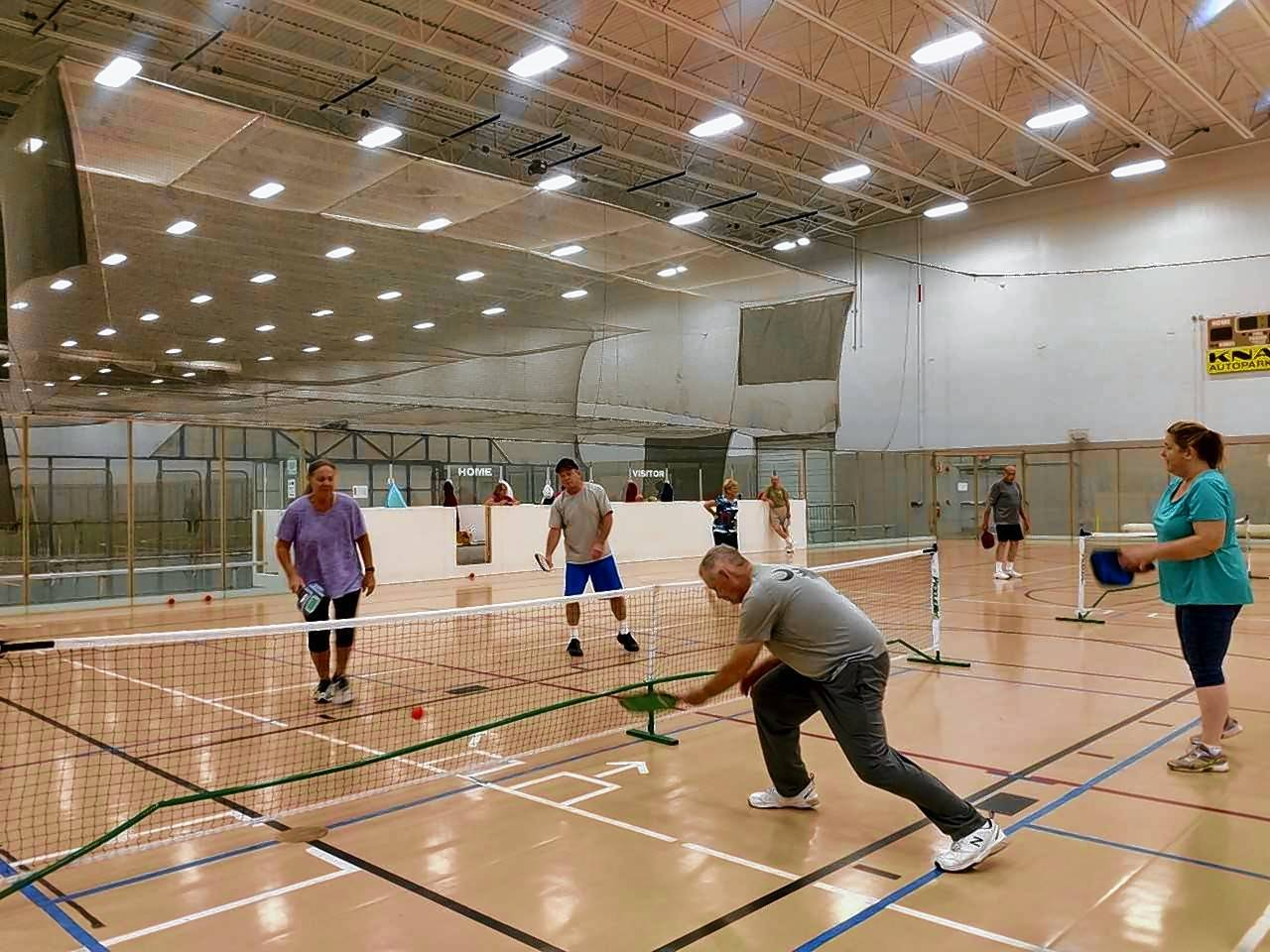 Courtesy of Sue MorrisAmy McGuan of Libertyville, left, teams with Greg Burgh of Grayslake at the net against Bill Morris of Grayslake and Cathy Freuger of Lake Villa during a pickleball match Wednesday at the Libertyville Sports Complex.