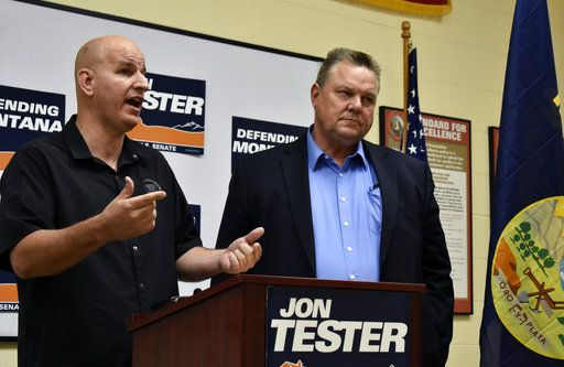 This Aug. 31, 2018 photo shows Montana U.S. Sen. Jon Tester, right, listening to Brandon Judd, president of the National Border Patrol Council, speak about border security and immigration during a campaign event in Billings, Mont. Outside groups and donors have poured more than $45 million into the race between Tester and Republican State Auditor Matt Rosendale.