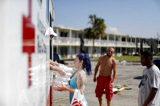 Crystal Williams receives food from the Red Cross outside a damaged motel, Tuesday, Oct. 16, 2018, in Panama City, Fla., where many residents continue to live in the aftermath of Hurricane Michael.