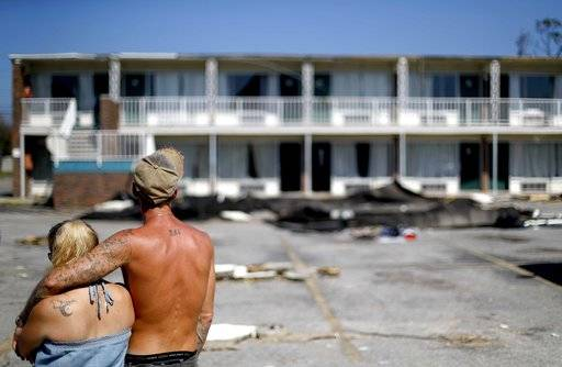 Residents line up for food from the Red Cross outside a damaged motel, Tuesday, Oct. 16, 2018, in Panama City, Fla., where many residents continue to live in the aftermath of Hurricane Michael. Some residents rode out the storm and have no place to go even though many of the rooms at the motel are uninhabitable.