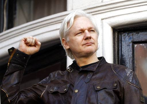 FILE - In this file photo dated Friday May 19, 2017, WikiLeaks founder Julian Assange looks out from the balcony of the Ecuadorian embassy in London. Newly released Ecuadorean government documents made public late Tuesday Oct. 16, 2018, by Ecuadorean opposition lawmaker Paola Vintimilla, have laid bare an unorthodox attempt to extricate Assange from his embassy hideaway in London by naming him as a political counselor to the country's embassy in Moscow. (AP Photo/Matt Dunham, FILE)