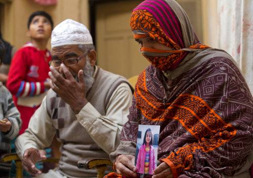 In this Jan. 18, 2018, file photo, Nusrat holds a picture of her daughter Zainab Ansari with her husband Mohammed Amin Ansari, left, in Kasur, Pakistan. Mohammad Imran, a serial killer of eight children, was executed at a Pakistani prison Wednesday morning, Oct. 17, 2018, after the country's top court rejected a request for his public hanging, officials said. Zainab's father Mohammed Amin Ansari was specially allowed to witness the execution. (AP Photo/B.K. Bangash, File)