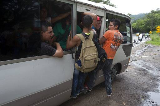Honduran migrants get a free ride from a driver during their caravan to the U.S., in Chiquimula, Guatemala, Tuesday, Oct. 16, 2018. U.S. President Donald Trump threatened on Tuesday to cut aid to Honduras if it doesn't stop the impromptu caravan of migrants, but it remains unclear if governments in the region can summon the political will to physically halt the determined border-crossers. (AP Photo/Moises Castillo)