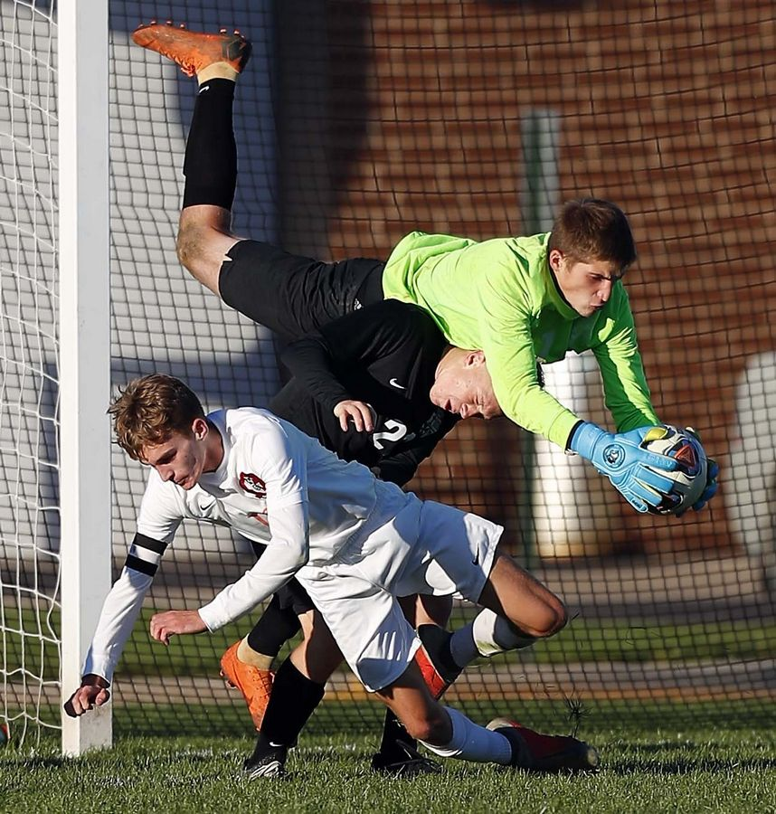 St. Edward keeper Evan Sajtar (1) goes up and over his teammate Cameron Kruk (21) for a save against Stillman Valley in the IHSA Class 1A sectional semifinal Wednesday in Genoa.