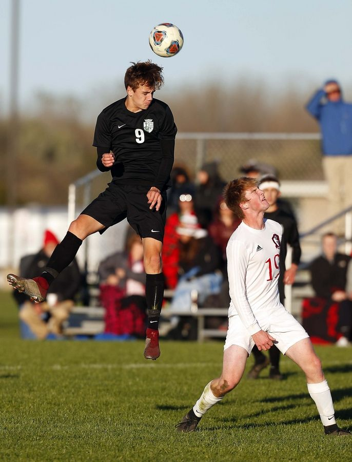 St. Edward's Jackson Godfrey (9) moves the ball over Stillman Valley's Clay Smith, (19) in the IHSA Class 1A sectional semifinal Wednesday in Genoa-Kingston.