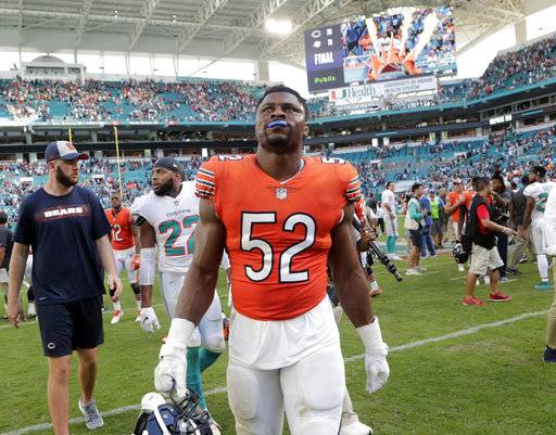 In this Oct. 14, 2018 photo Chicago Bears outside linebacker Khalil Mack (52) walks off the field at the end of an NFL football game against the Miami Dolphins in Miami Gardens, Fla. No matter how dominant Mack is, New England Patriots coach Bill Belichick wanted to make one thing clear on Wednesday, Oct. 17, 2018. He's no L.T. Belichick says he won't put Mack or anyone else in Hall of Famer Lawrence Taylor's class. The Patriots visit the Bears this week and that means Belichick will get an up-close look at one of the game's top outside linebackers, assuming Mack is ready to play after injuring his ankle last week. (AP Photo/Lynne Sladky)