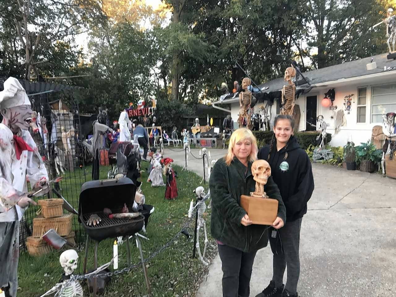 The family always went all out in their Halloween decorations, and the ashes of Michael Podlin, who died of cancer last year, are in a box topped with a skull with light-up red eyes, held by his widow, TammySue Margalit, and their daughter, Ginger.