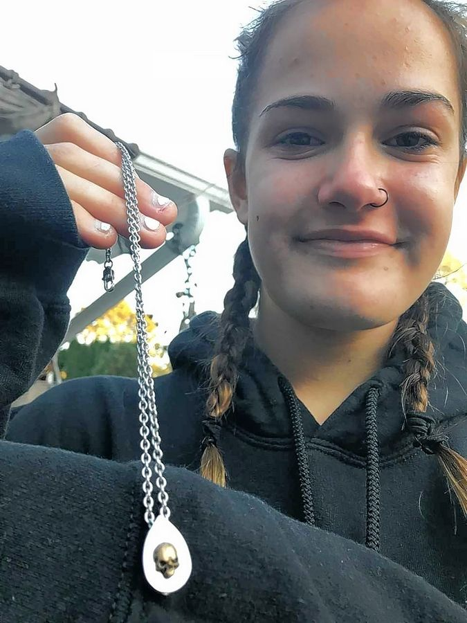 Alternating between smiling at the memories and crying at the reality, Ginger Podlin holds a gift from her father -- a skull necklace that holds a bit of his ashes.