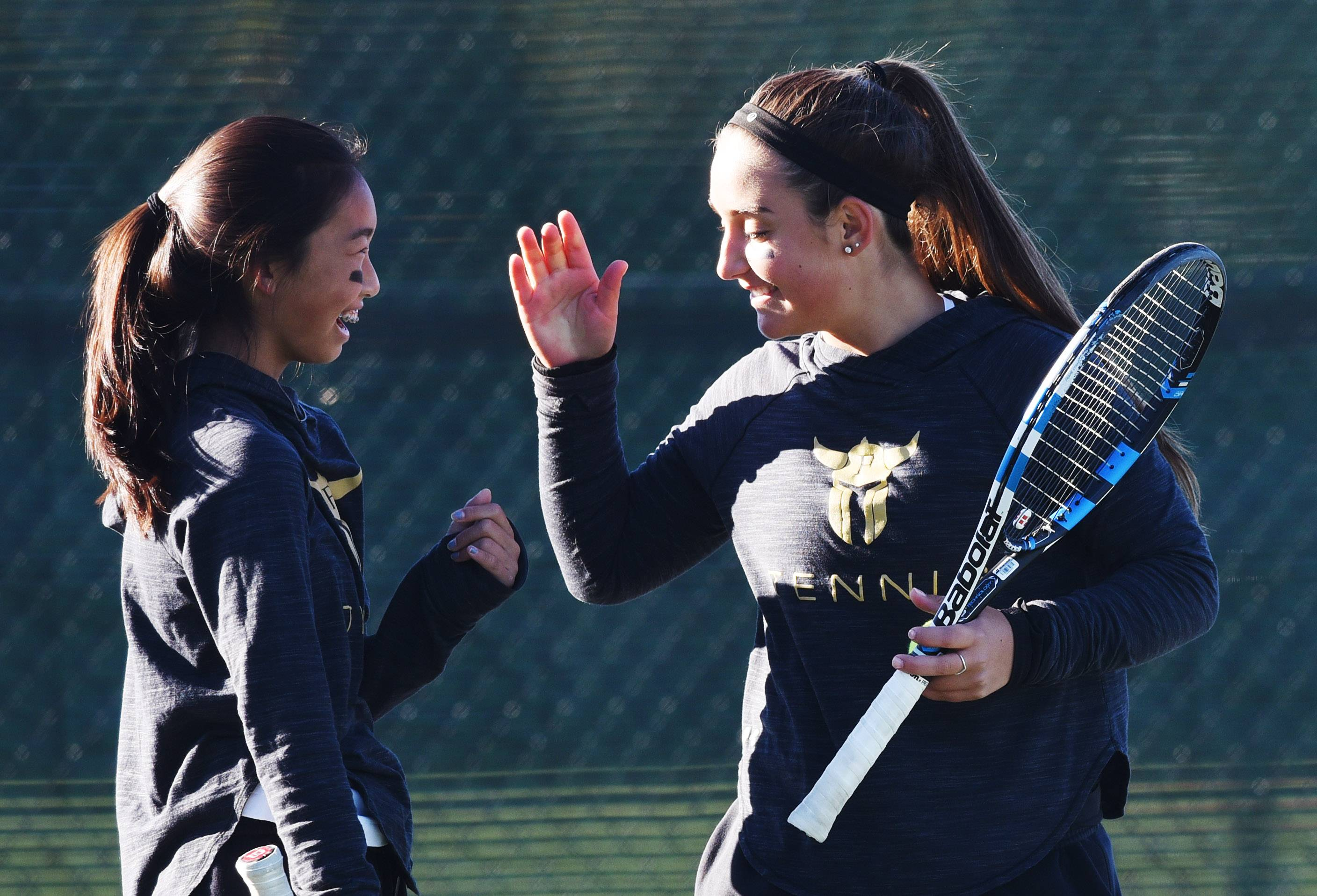 Fremd doubles players Akari Matsuno, left, and Kyra Emmanouilidis congratulate one another following a point during the girls state tennis tournament in Palatine Thursday.