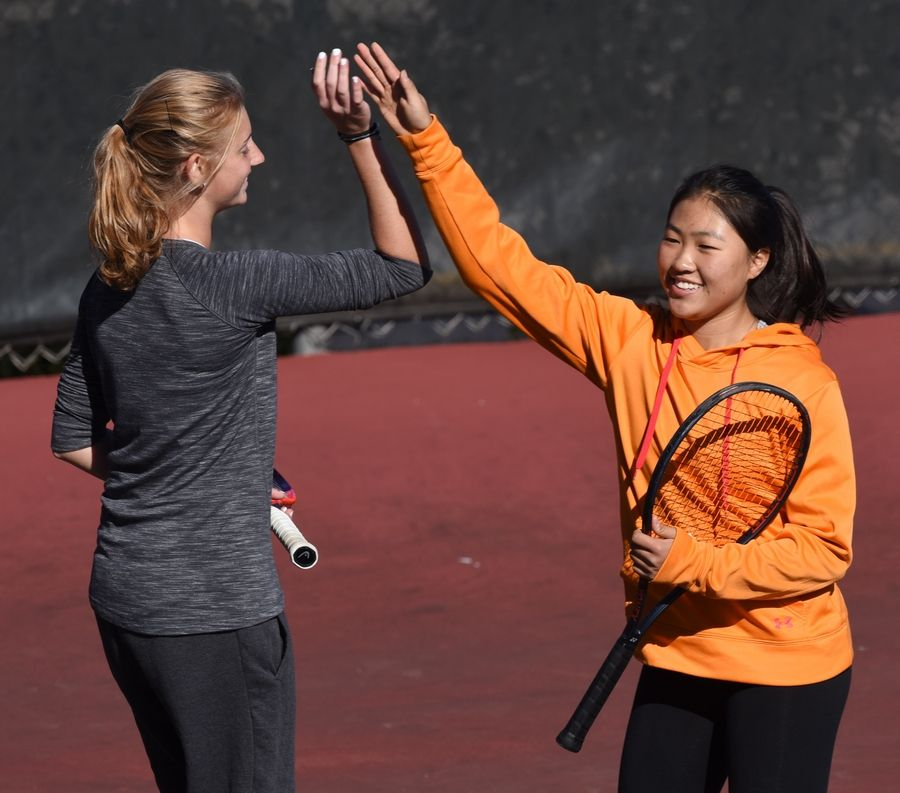 Wheaton-Warrenville South doubles players Emily Orlove, left, and Samantha Choi congratulate one another following a point while playing against Mundelein during the girls state tennis tournament at Elk Grove Thursday.