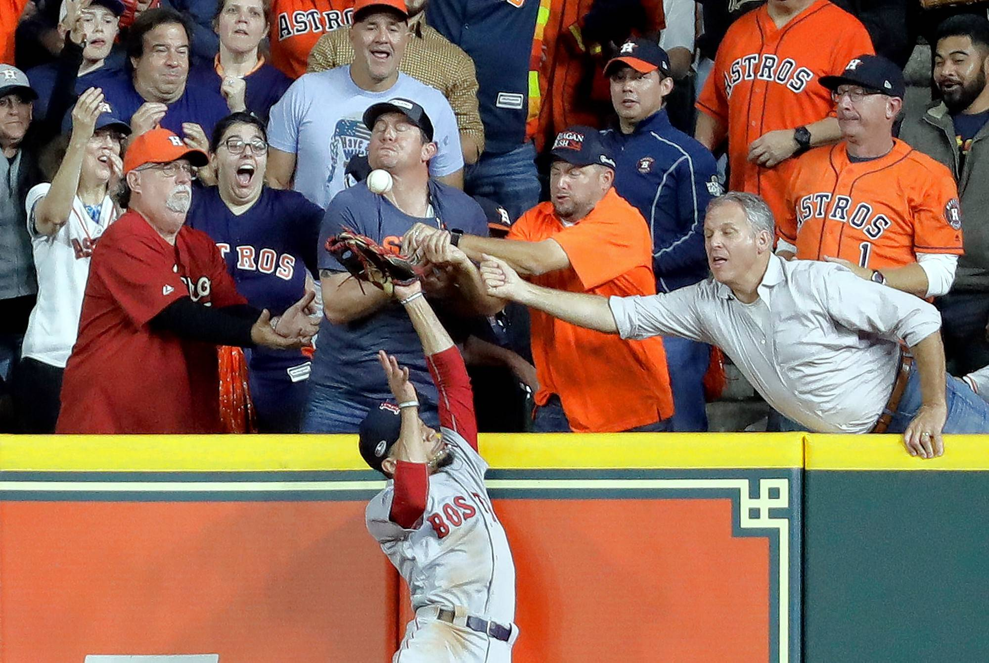 Fans interfere with Boston Red Sox right fielder Mookie Betts trying to catch a ball hit by Houston Astros' Jose Altuve during the first inning in Game 4 of a baseball American League Championship Series on Wednesday, Oct. 17, 2018, in Houston. Altuve was called out.