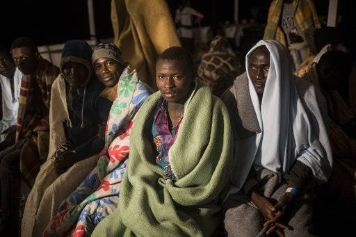Vafin, 16, centre, from Guinea Conarky, sits with other migrants on the deck of Open Arms vessel, after they were rescued by the Spanish NGO Pro Activa Open Arms, about 40 miles (64 kms) from the Spanish coasts, on Thursday, Oct. 11, 2018. The Open Arms is now based at Motril port in order to start operating in the western Mediterranean area.