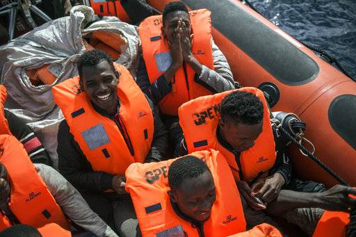 Migrants celebrate on a rescue boat from the Spanish NGO Pro activa Open Arms after being spotted and rescued them at Alboran Sea, about 40 miles (64 kms) from the Spanish coasts, on Thursday, Oct. 11 2018. The Open Arms is now based at Motril port in order to start operating in the western Mediterranean area.