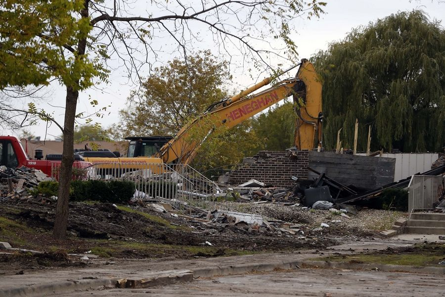 Remains of condominium buildings heavily damaged by fire three months ago in Prospect Heights were being demolished Friday to clear land for new construction and the expected return of displaced residents next year.