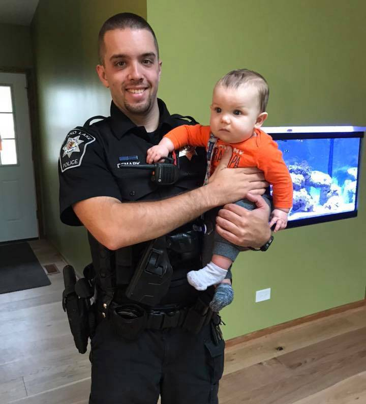 "Island Lake police officer Jason DeMark with Seth, the baby he rescued from a burning home in May. ""Without him and the Wauconda Fire Department's ridiculously quick response and preparedness, our story would be dramatically different,"" Seth's mom wrote of the dramatic rescue."