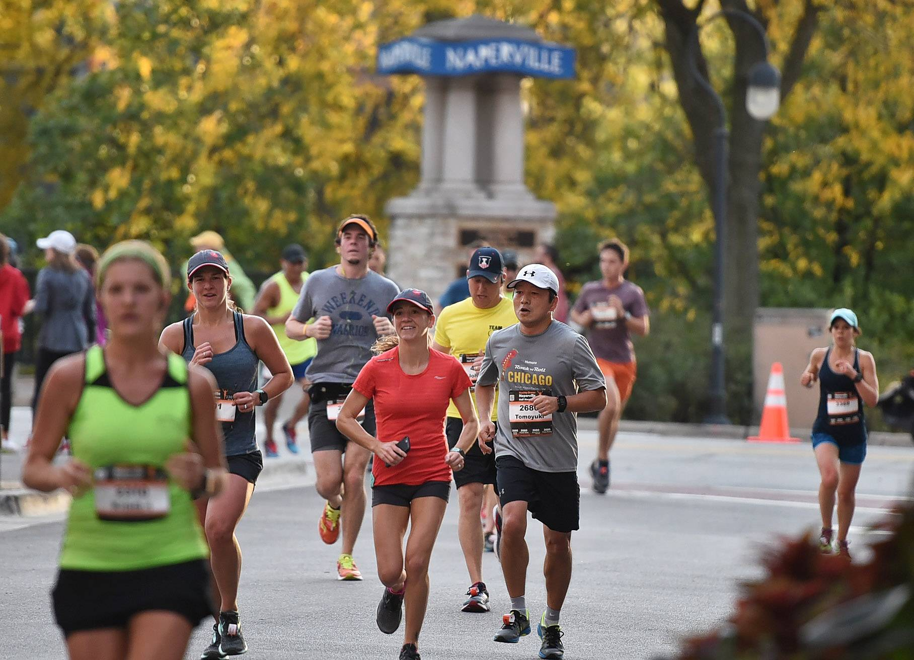 Runners proceed along Water Street during the Healthy Driven Half Marathon in downtown Naperville. While it causes a 27 percent spike in parking demand, its early morning timing means customers of downtown businesses aren't affected, the race director says.