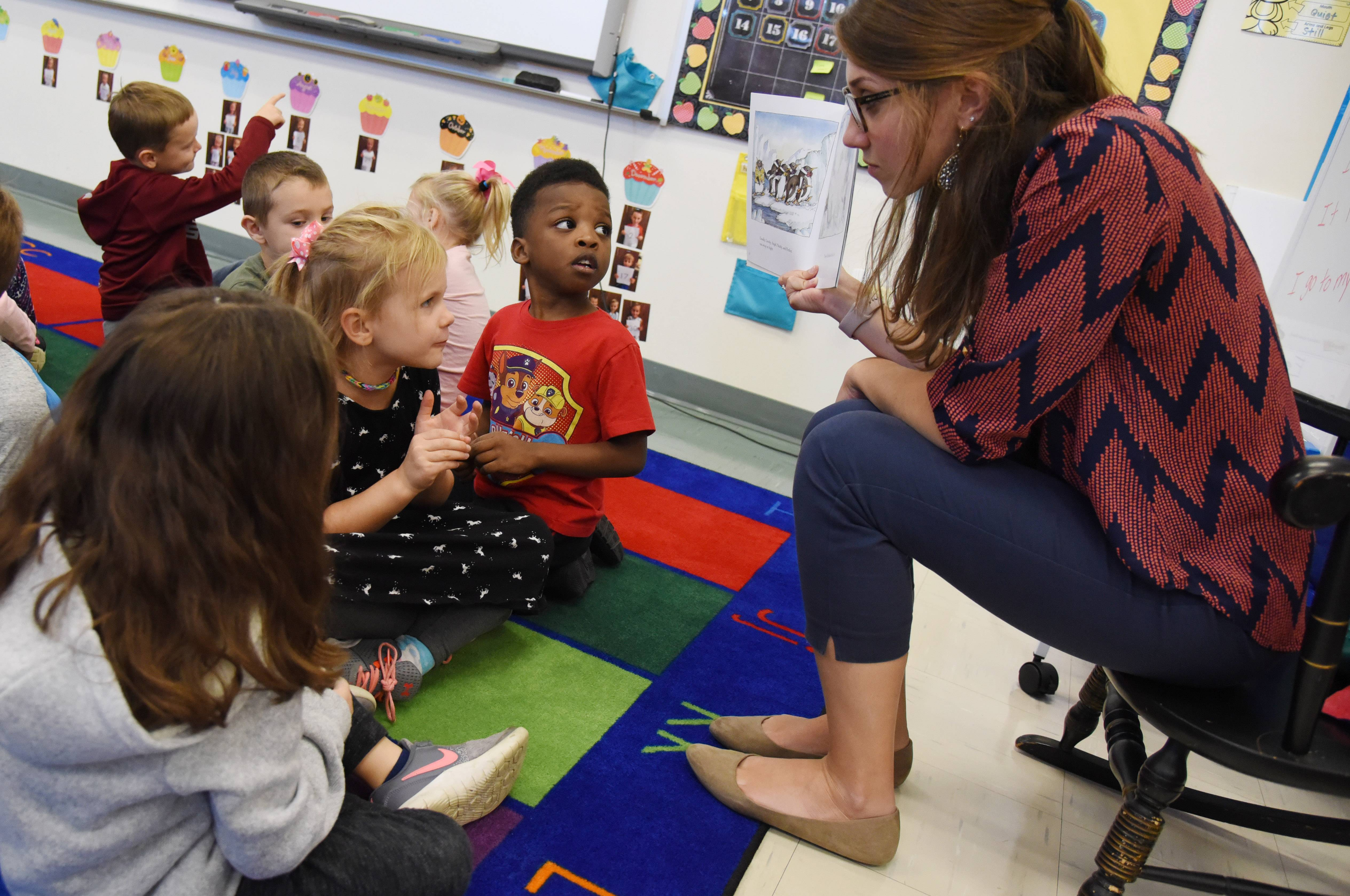 Hawthorn Elementary kindergarten teacher Abby Udelhofen, right, has a book discussion with students Kelly Shields and Makai Brewster Wednesday at the Elmhurst school.