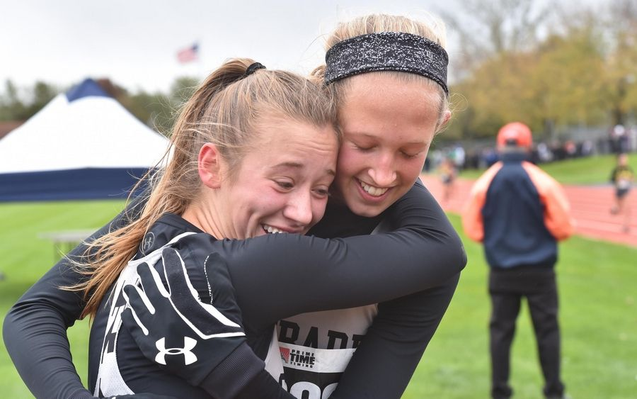 Glenbard East's Lindsey Novak, left, and Maddie Weltin celebrate their finishes at the Class 3A Lake Park cross country regional meet Saturday in Roselle.