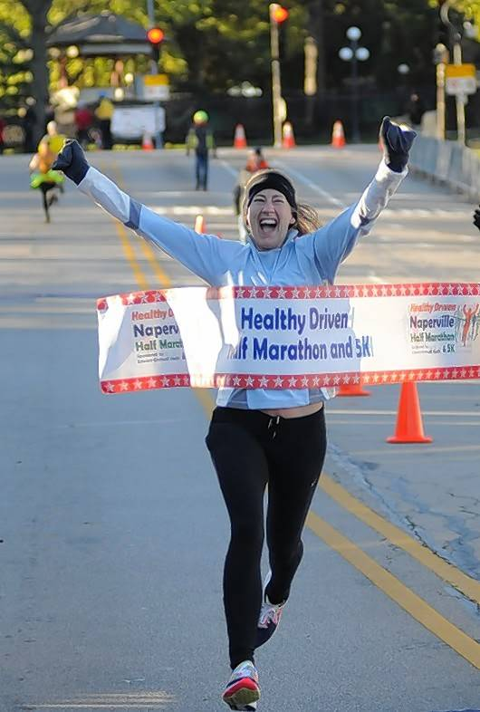 Erika Edmonson raises her arms in celebration Sunday as she crosses the finish line in the Healthy Driven Naperville Half Marathon. Edmonson, of Riverside, was the top woman finisher, with a time of 1 hour, 24 minutes.