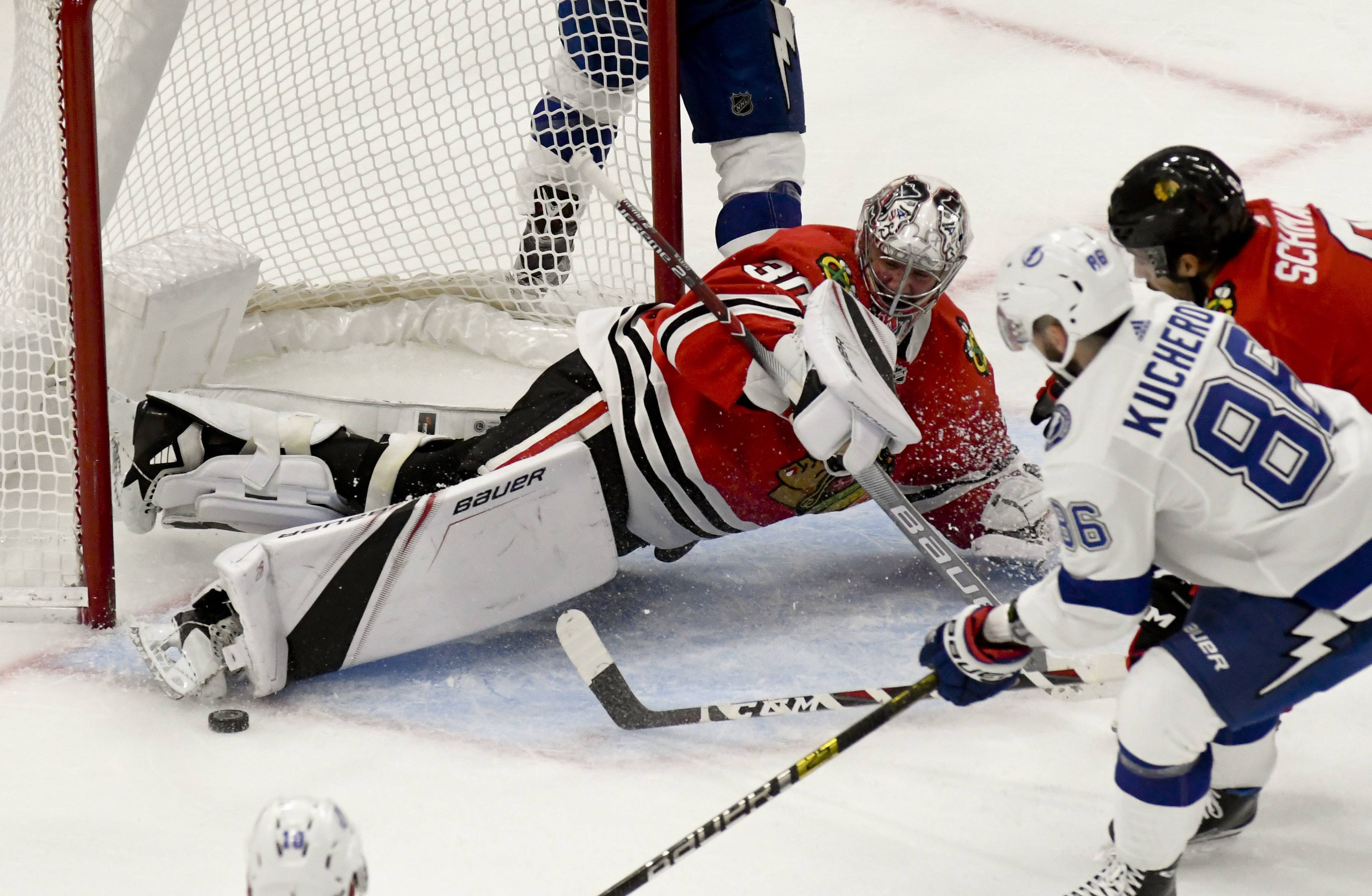 Chicago Blackhawks goaltender Cam Ward (30) and center Nick Schmaltz (8) defend against Tampa Bay Lightning right wing Nikita Kucherov (86) during the second period of an NHL hockey game on Sunday Oct. 21, 2018, in Chicago. (AP Photo/Matt Marton)