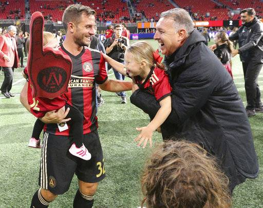Atlanta United head coach Gerardo Martino, front right, and Kevin Kratz, left, celebrate after clinching a playoff spot with a victory over the Chicago Fire at an MLS soccer match on Sunday, Oct. 21, 2018, in Atlanta. (Curtis Compton/Atlanta Journal-Constitution via AP)