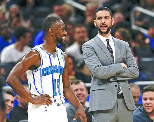 Charlotte Hornets' Kemba Walker (15) talks with head coach James Borrego while waiting for a teammate to shoot a free throw against the Orlando Magic during the second half of an NBA basketball game, Friday, Oct. 19, 2018, in Orlando, Fla. (AP Photo/John Raoux)