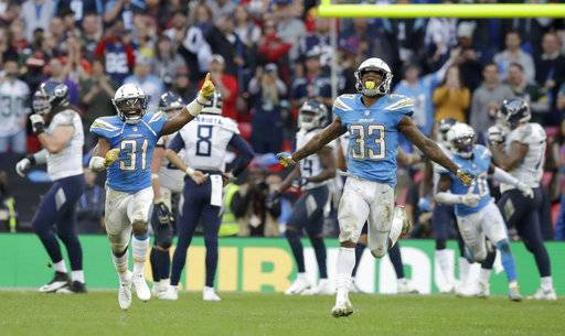Los Angeles Chargers defensive back Adrian Phillips (31) and free safety Derwin James (33) celebrate after a successful defensive play near the end of the second half of an NFL football game against Tennessee Titans at Wembley stadium in London, Sunday, Oct. 21, 2018. Los Angeles Chargers won the match 20-19. (AP Photo/Matt Dunham)