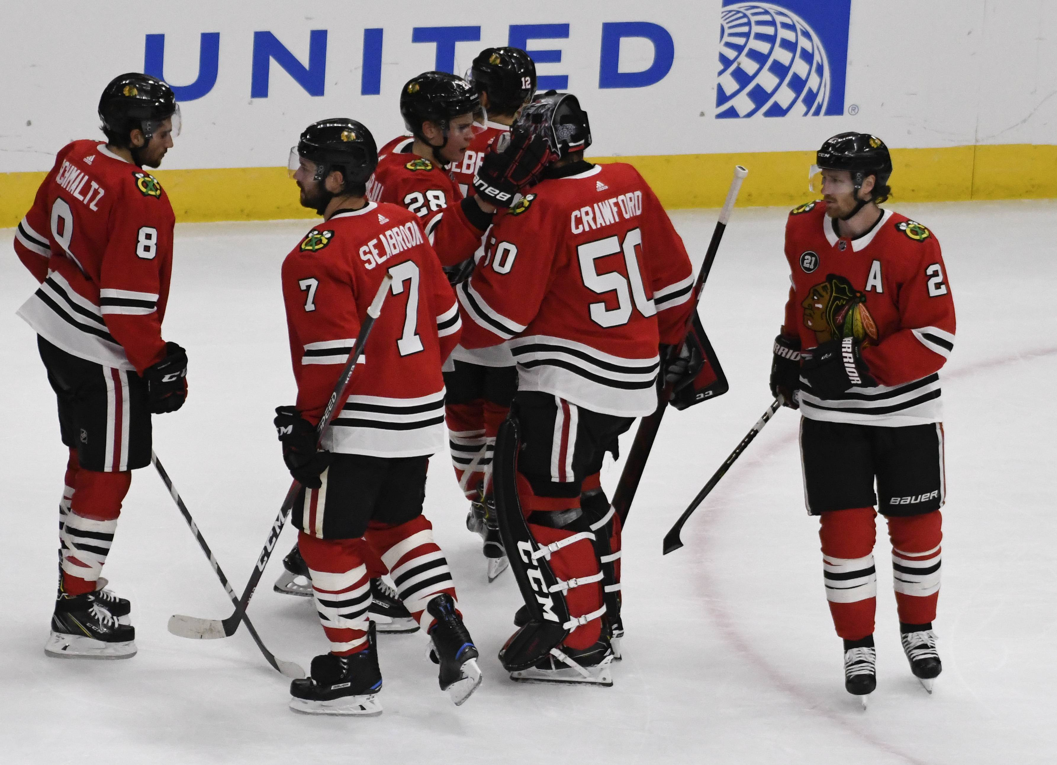 Chicago Blackhawks goaltender Corey Crawford (50) is greeted by his teammates after playing in first game after an injury in an NHL hockey game against the Arizona Coyotes Thursday, Oct. 18, 2018, in Chicago. The Coyotes won 4-1. (AP Photo/David Banks)