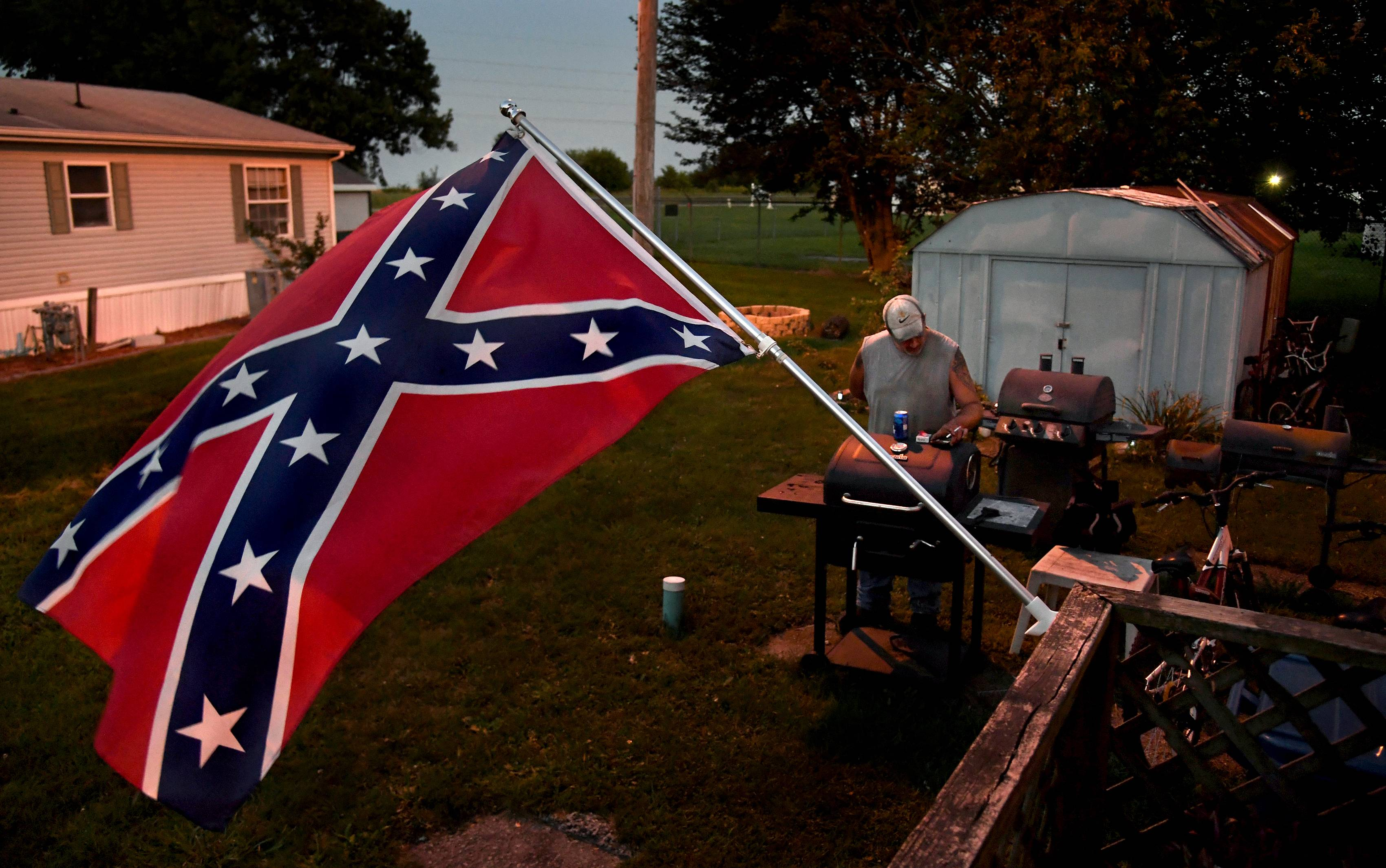 Brent Lowe checks his phone in the yard of his mobile home, where a Confederate battle flag flies daily. Lowe says he feels that flying the Confederate flag is more an act of rebellion than a political statement. MUST CREDIT: Washington Post photo by Michael S. Williamson