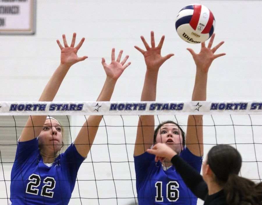 St. Charles North's Cailey Johns, left, and Grace Lilly, right, block against Streamwood during regional play in varsity girls volleyball at St. Charles North Tuesday night.