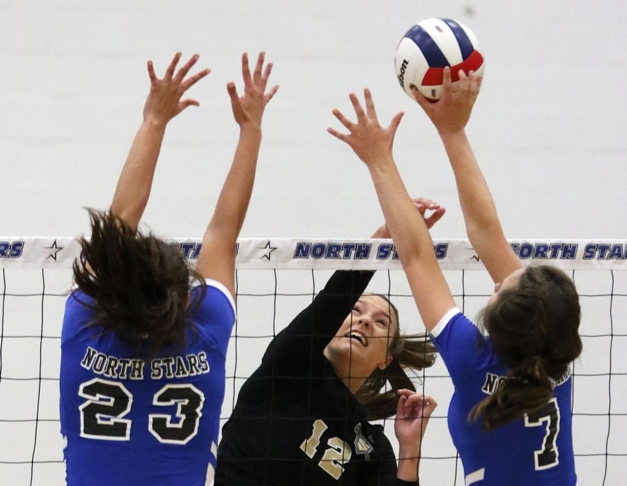 Streamwood's Ava Sumoski, center, slams the ball over the net as St. Charles North's Marissa Guajardo, left, and Kyla Lannert block during regional play in varsity girls volleyball at St. Charles North Tuesday night.