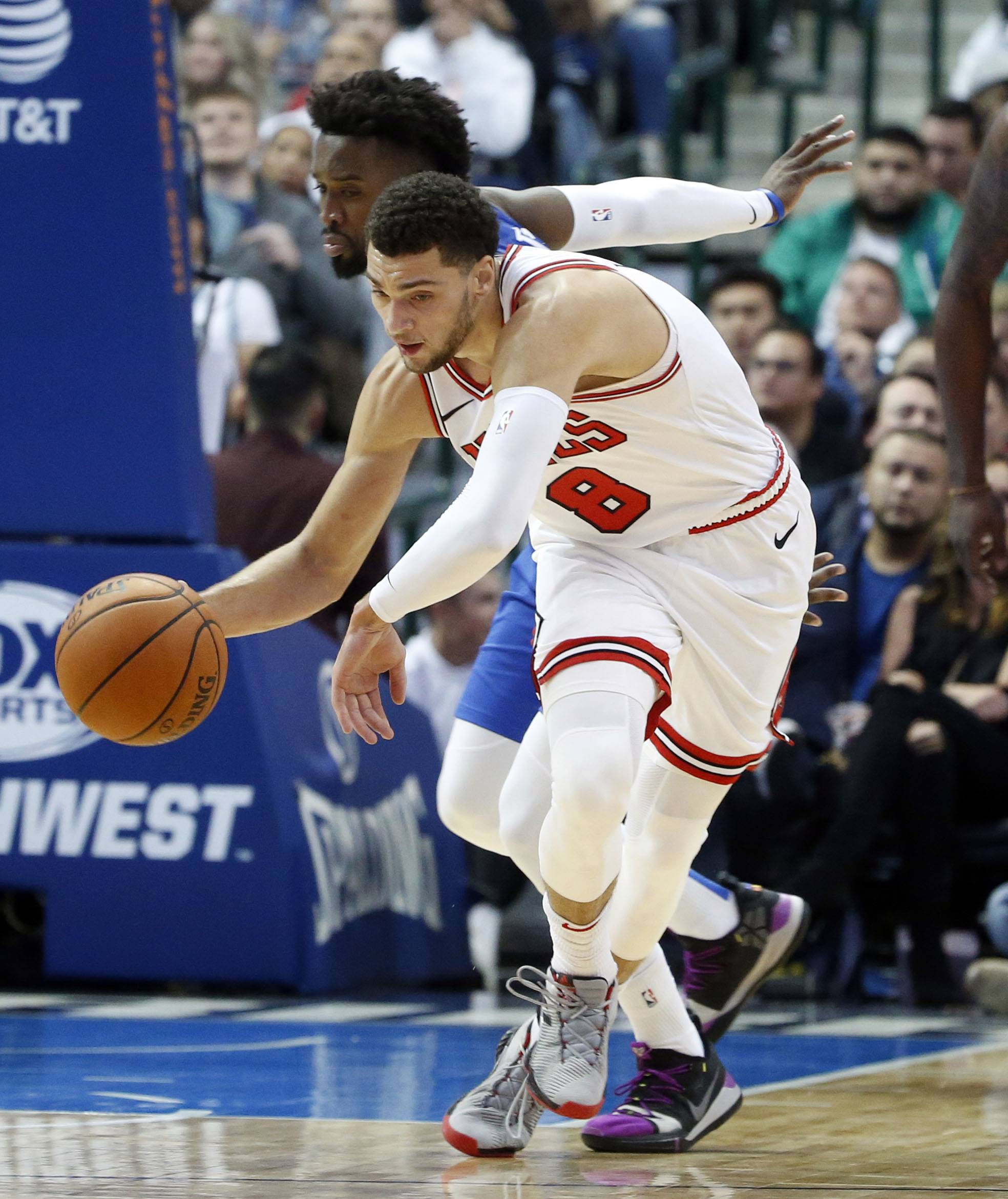 Chicago Bulls guard Zach LaVine (8) dribbles the ball past Dallas Mavericks guard Wesley Matthews during the first half of an NBA basketball game in Dallas, Monday, Oct. 22, 2018. (AP Photo/Michael Ainsworth)