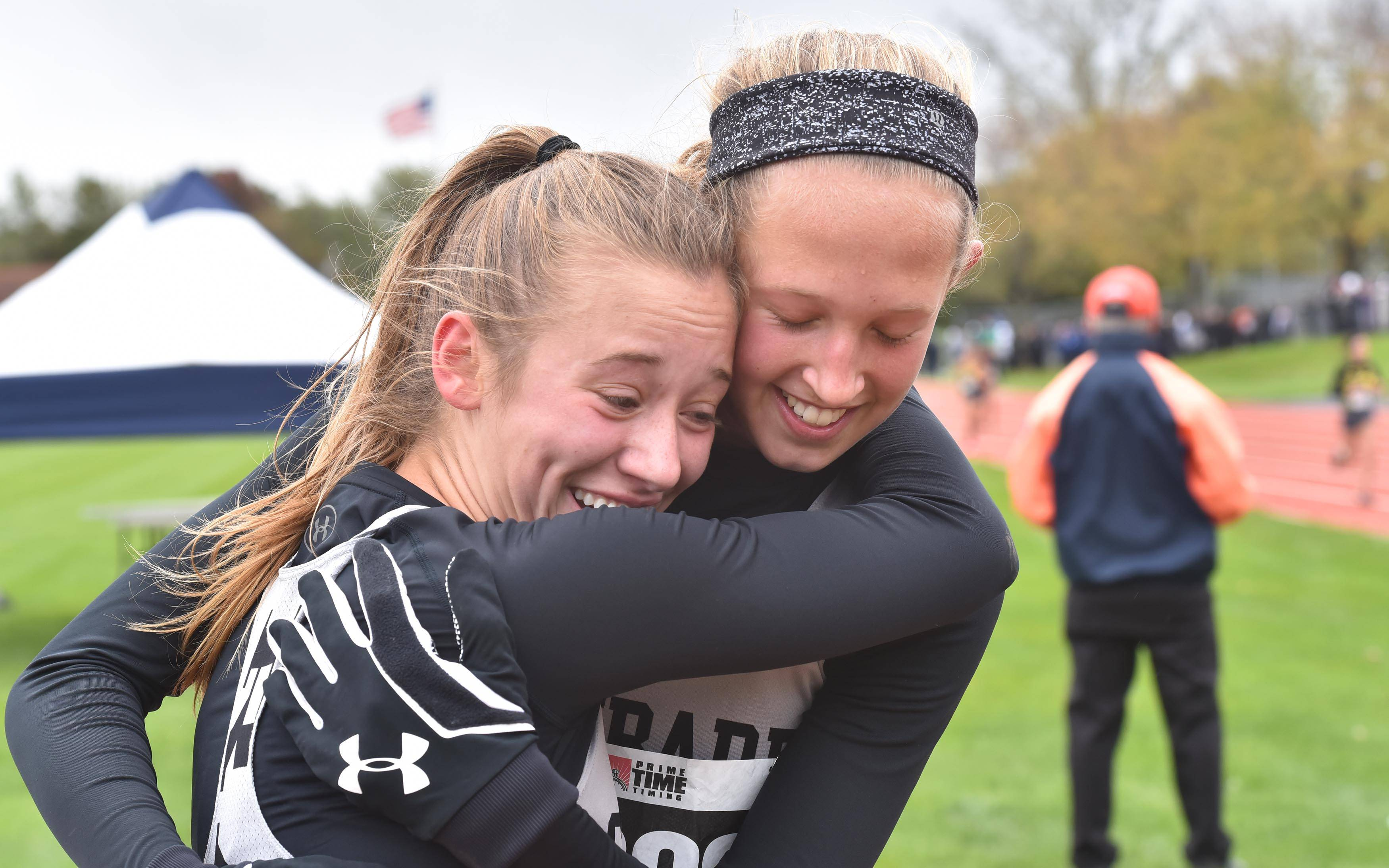Glenbard East's Lindsey Novak, left, and Maddie Weltin celebrate at the finish of the Class 3A Lake Park cross country regional meet Saturday in Roselle.