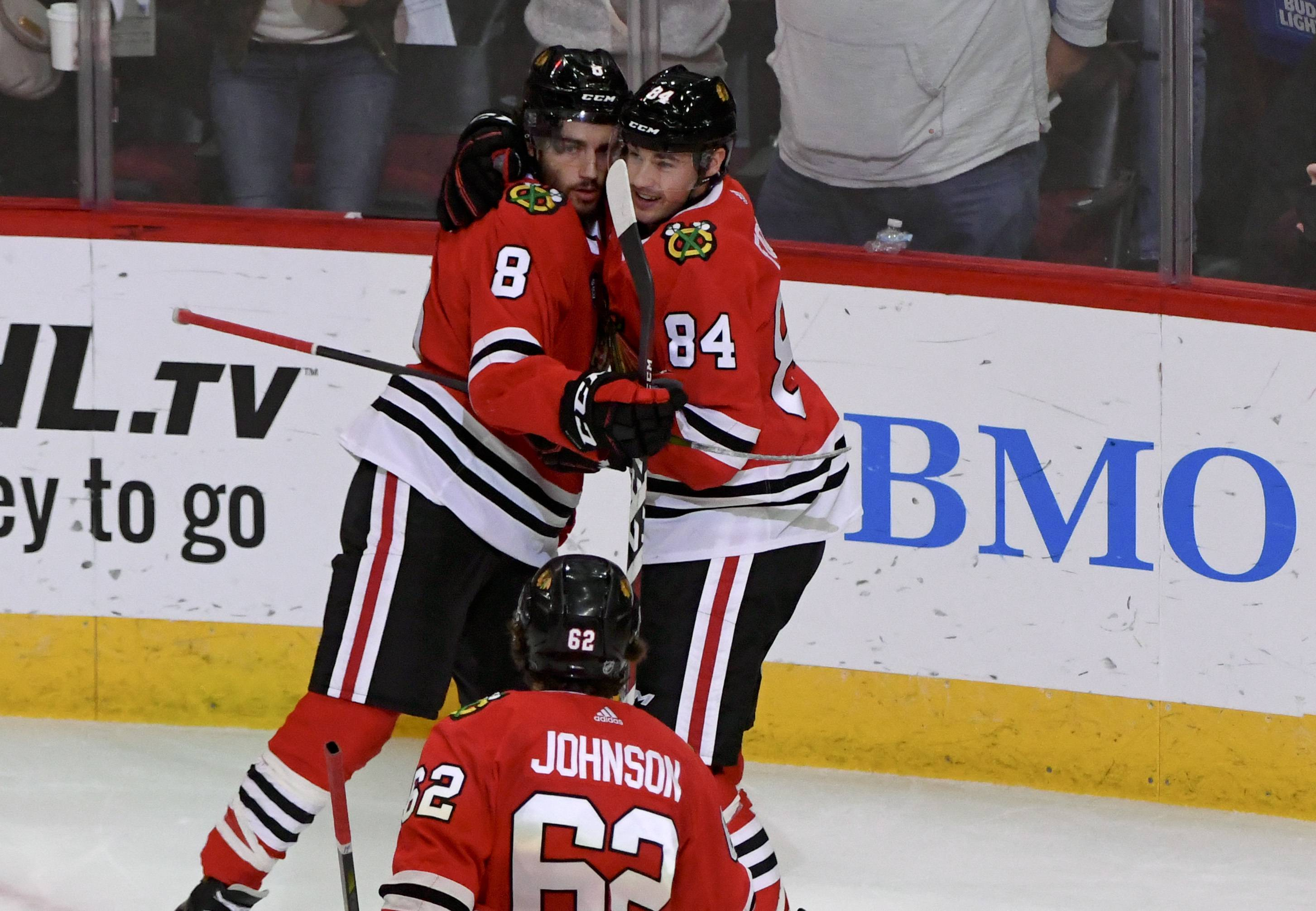 Chicago Blackhawks center Nick Schmaltz (8) hugs left wing Alexandre Fortin (84) after Fortin scored a goal against the New York Rangers during the second period of an NHL hockey game on Thursday Oct. 25, 2018, in Chicago.