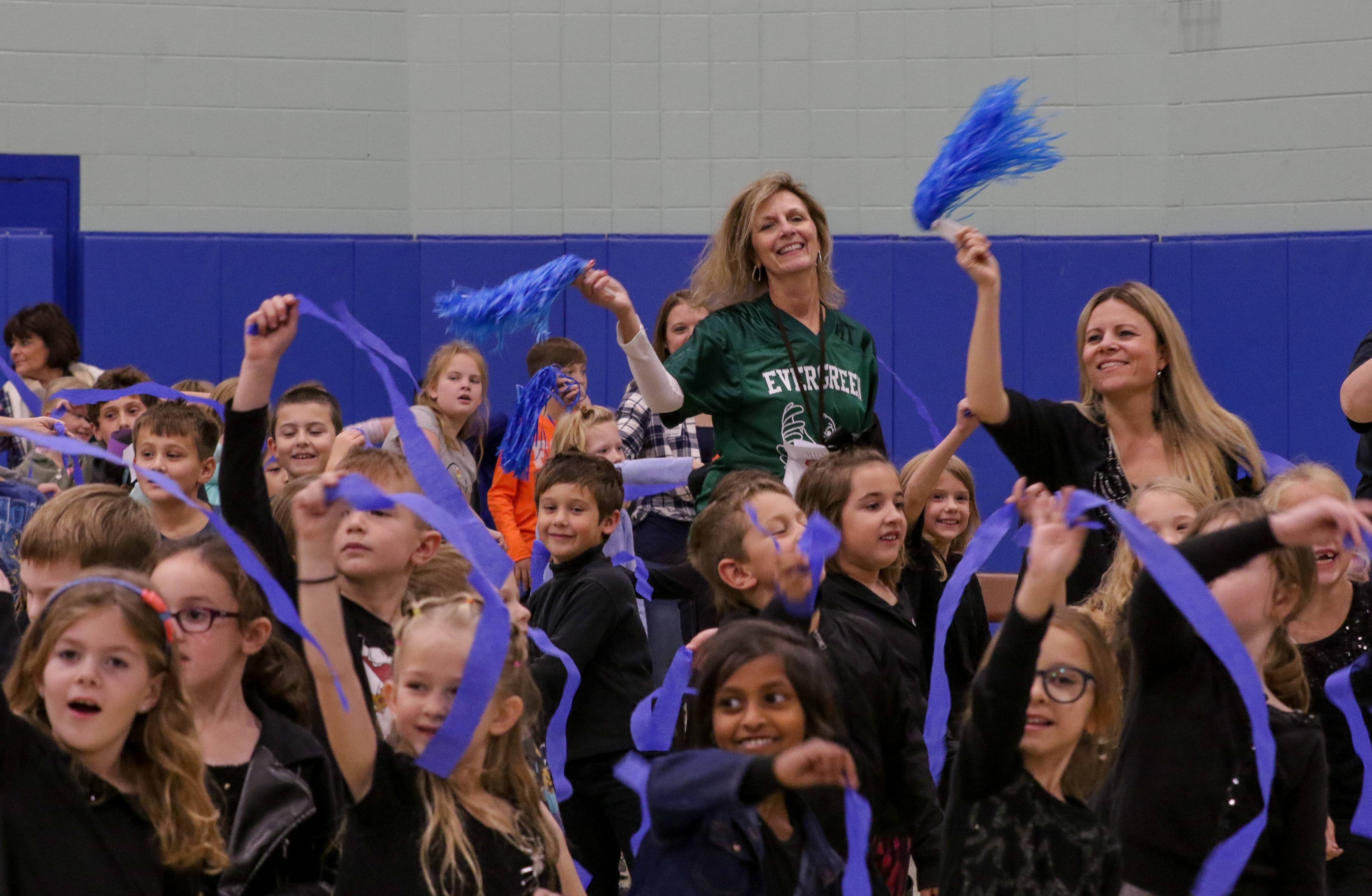 Evergreen Principal Laura Pfanenstiel, center, waves blue pom poms with students as a nod to the 2018 National Blue Ribbon Award.