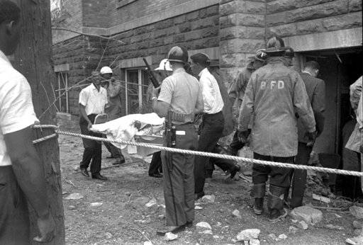"FILE - In this Sept. 15, 1963, file photo, firefighters and ambulance attendants remove a covered body from the 16th Street Baptist Church in Birmingham, Ala., after by a deadly explosion detonated by members of the Ku Klux Klan during services. The 2018 mail-bomb scare has reopened old wounds for Lisa McNair, whose life has been shaped by the blast that occurred a year before she was born, killing her sister, Denise, 11. ""It's like, 'Ugh, again.' When are we going to get this right?"" asked McNair. ""It's been 55 years since Denise was killed. Why do we keep going there in America? Why do we keep going there as a world and human beings?"""