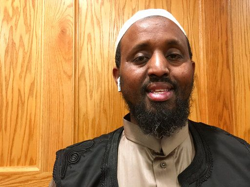 "Mohamed Omar, executive director of Dar Al-Farooq Islamic Center, poses for a portrait in Bloomington, Minn. on Thursday, Oct. 25, 2018. The center was bombed just before morning prayers when the attackers broke a window to the imam's office and threw a pipe bomb containing black powder inside, sparking a fire that caused extensive damage. Three men from Illinois were charged in the attack; according to charges, one of them said the purpose was to ""scare"" Muslims out of the United States. Omar said the new mail-bomb case and the attack on his mosque were both intended to ""create fear and terrorize people."""