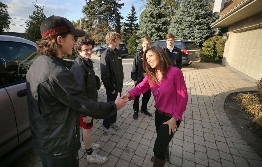 "Linda DiFranco, right, of Park Ridge shakes hands with the five Maine South High School hockey players who helped save her house from a fire last Monday night. ""This would have lit up like a Christmas tree,"" she said, if not for the boys' quick actions."