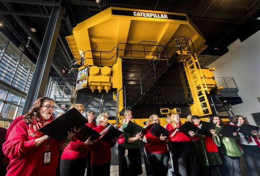 "In this 2017 photo, the Caterpillar Employee Mixed Chorus sings holiday songs as guests  celebrate a ""Light up the Holidays"" event in 2017 at the Doug Oberhelman Caterpillar Visitors Center in downtown Peoria. Peoria wasn't always a company town. It was a distillery town, a farm implement town and a river town before the Caterpillar Tractor Co. set up shop in the 1800's. A bond developed between company and town that became a mutually-beneficial relationship. While Caterpillar is moving 300 executive and staff jobs to Dearfield, Ill., 12,000 employees remain in central Illinois.(Fred Zwicky/Journal Star via AP)"