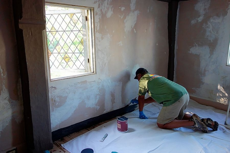 A specialty craftsman repairs plaster on the walls at the James Blake House. The plaster work on the walls is rough and uneven compared to the style of modern homes.