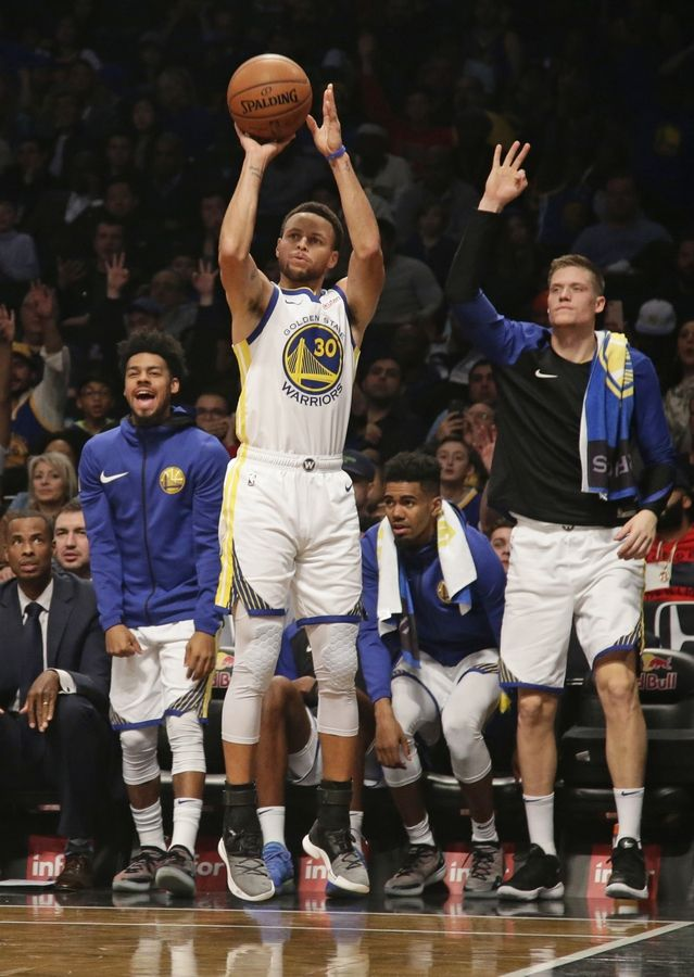 53131914a2ac Golden State Warriors react as teammate Stephen Curry shoots a three-point  basket during the