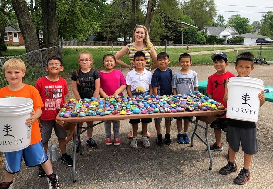 Round Lake Beach Elementary School art teacher Annie Adamski poses with students who came up with the idea to ask landscaping companies to help beautify their school.