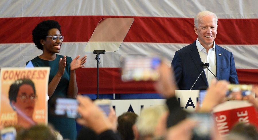 Former Vice President Joe BIden comes on stage after being introduced by congressional candidate Lauren Underwood, left, at the Kane County Fairgrounds Wednesday.