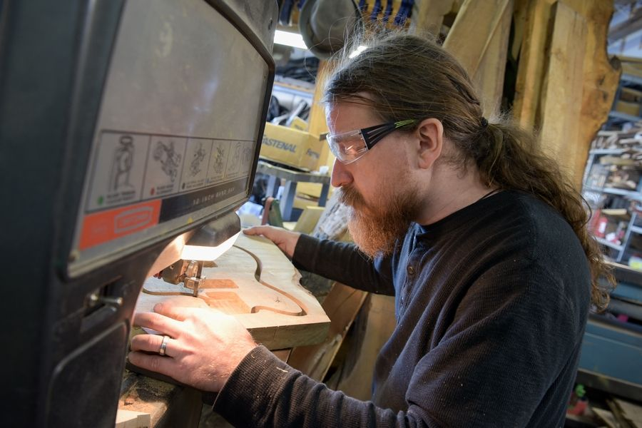 Phil Kurasz, a guitar technician at DeMont Guitars in Oswego, cuts the shape of the body of what became the DeMont Verb, a handmade guitar fashioned from pieces of the former Hobson Oak near Naperville and Woodridge.