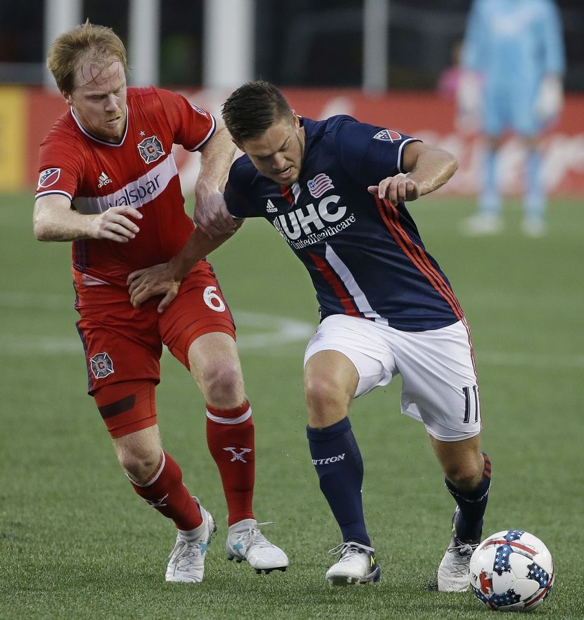 New England Revolution midfielder Kelyn Rowe (11) fends of Chicago Fire midfielder Dax McCarty (6) as Rowe makes a move to the goal during the first half of their MLS Soccer match, Saturday, June 17, 2017, in Foxborough, Mass.