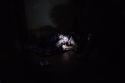 A Central American migrant named Enrique looks at the news from Honduras on his mobile phone, with his son Ian on his back, as they rest for the night at an abandoned hotel in Matias Romero, Oaxaca state, Mexico, Thursday, Nov. 1, 2018. TThousands of migrants arrived in the town of Matias Romero after an exhausting 40-mile (65-kilometer) trek from Juchitan, Oaxaca, where they failed to get the bus transportation they had hoped for.