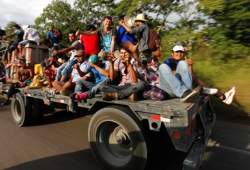 Central American migrants, part of the caravan hoping to reach the U.S. border, get a ride on a truck, in Donaji, Oaxaca state, Mexico, Friday, Nov. 2, 2018. The migrants had already made a grueling 40-mile (65-kilometer) trek from Juchitan, Oaxaca, on Thursday, after they failed to get the bus transportation they had hoped for. But hitching rides allowed them to get to Donaji early, and some headed on to a town even further north, Sayula.